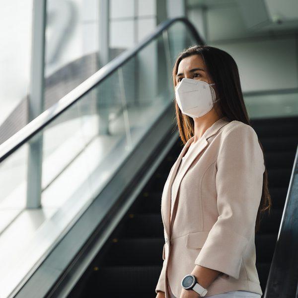 person near escalator in white face mask